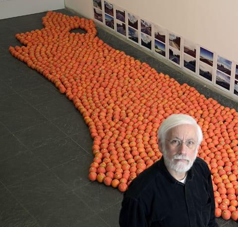 אבנר בר-חמא על רקע מיצב התפוזים בתצלום המופיע על כריכת הספר