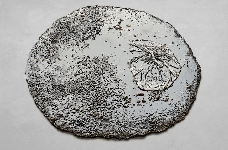 Marlie Mul, Puddle (Black Market), 2013, Sand, stones, resin, plastic bag, 2 x 80 cm. Courtesy: the artist and Croy Nielsen, Berlin